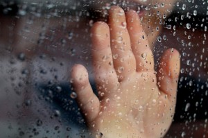 hand on rainy glass window