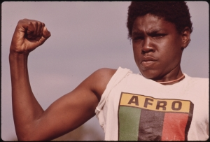 A young, black man showing his muscle during a small community program in Chicago.